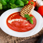 Smooth and sweet tomato soup, seasoned with basil, garlic